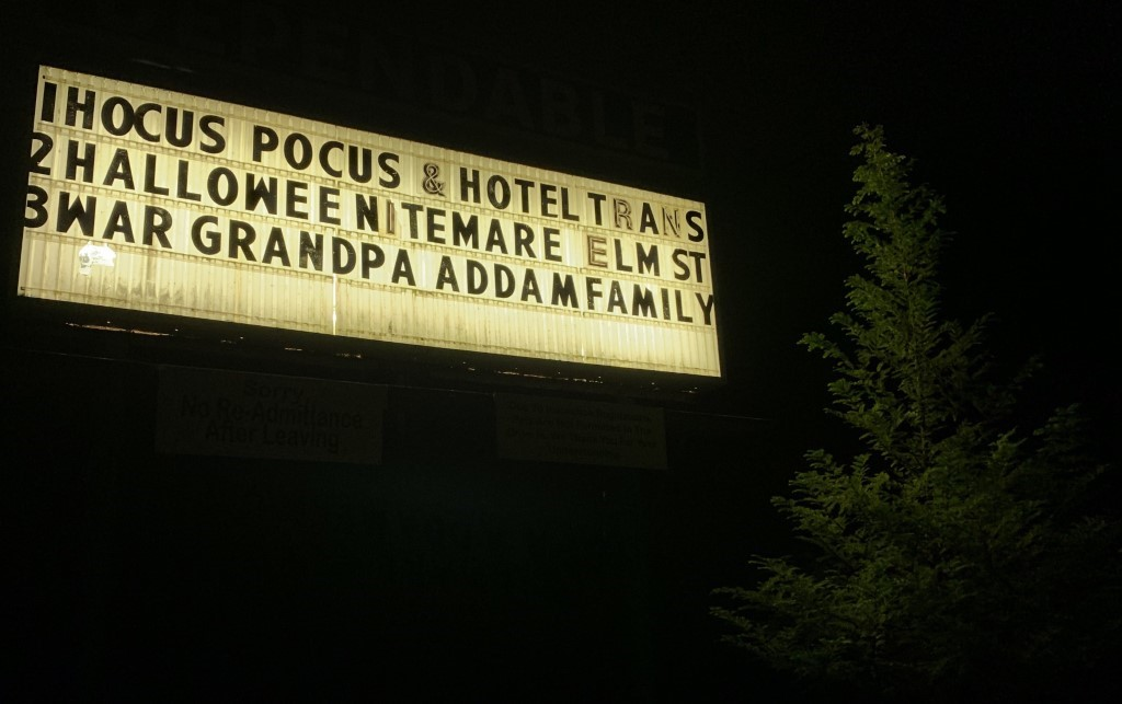 Photo of Dependable Drive In's Now Showing sign, listing several Halloween movies